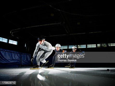 Three short track speed skaters racing around corn