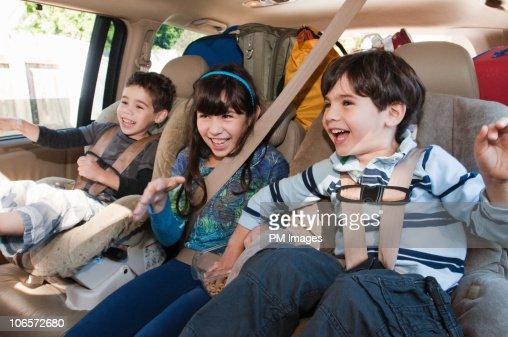 Three siblings in back seat of car