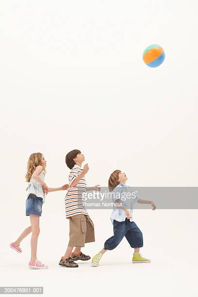 Three siblings (7-11) playing with beach ball, looking up, side view