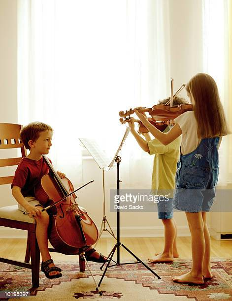 Three siblings (5-9) practicing cello and violins