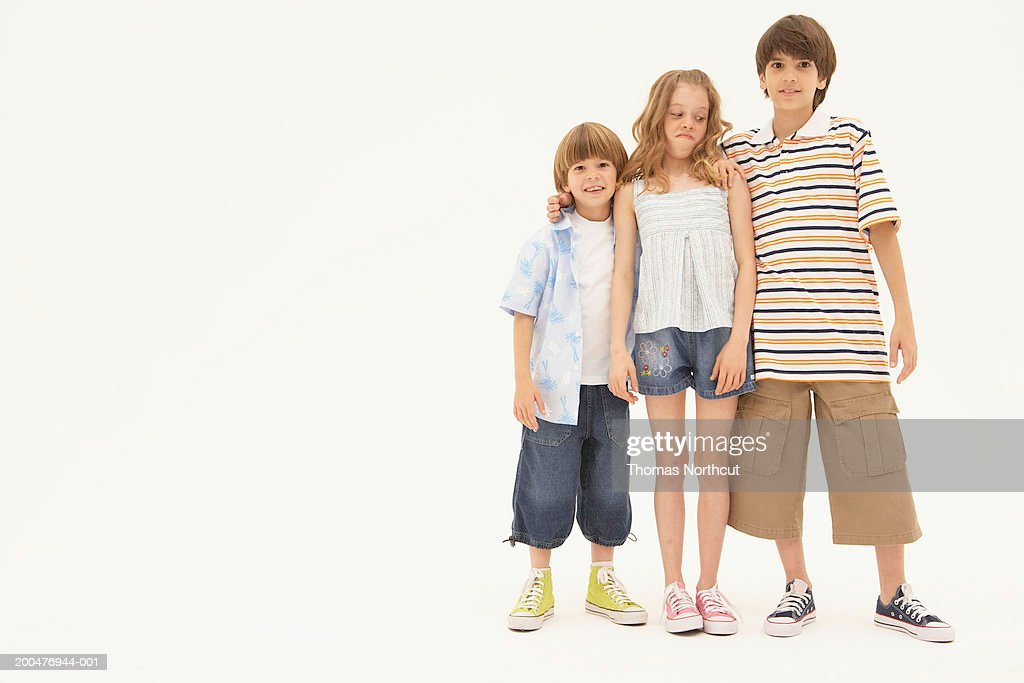 Three siblings (7-11) standing side by side : Stock Photo