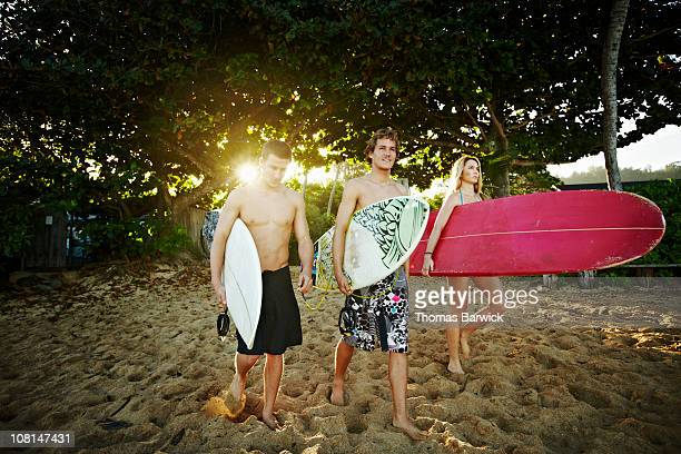 Three siblings walking onto beach with surfboards