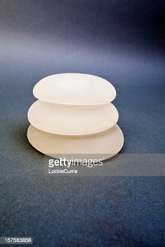 Three silicone breast implants on a background