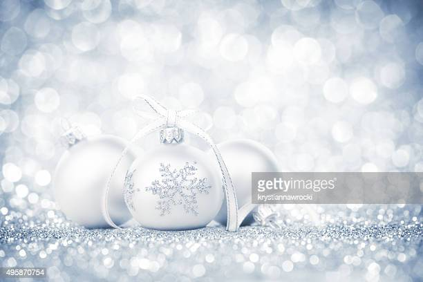 Three silver bauble with snowflake decoration and ribbon on glitter