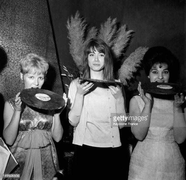 Three Singers receive a chocolate disc and eat it for our photographer Petula Clark Francoise Hardy and Rosy Armen on January 30 1963 in Paris France