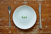three single peas on plate knife and fork inadequate nutrition