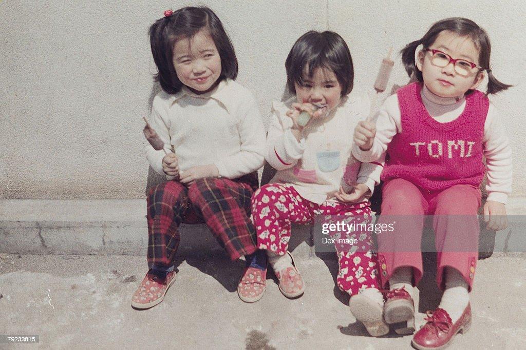 Three sisters eating ice-cream : Stock Photo