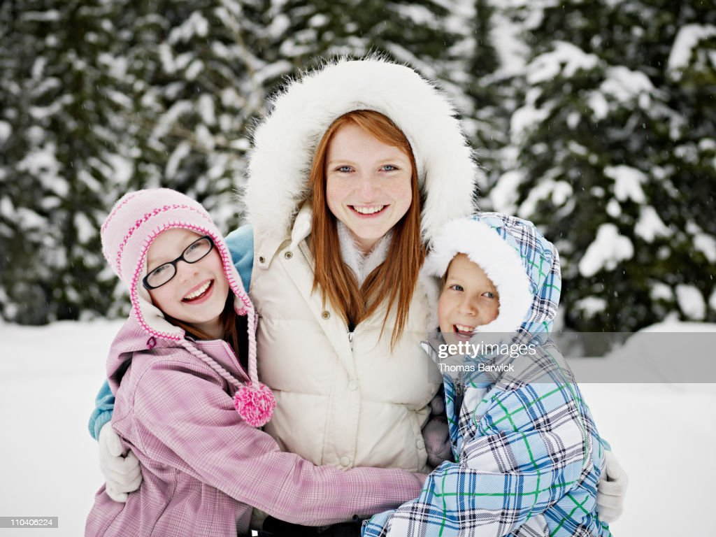Three sisters hugging and laughing in the snow : Stock Photo