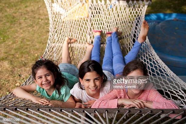 Three sisters lying in hammock