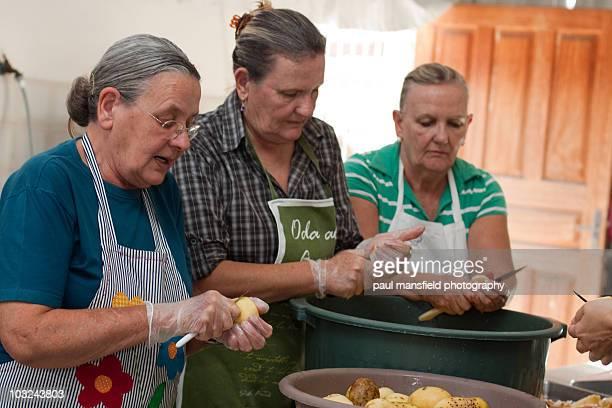 Three sisters peeling potatoes