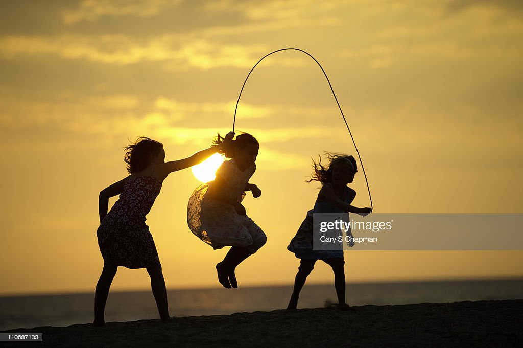 Three sisters play jumprope on beach in Hawaii : Stock Photo