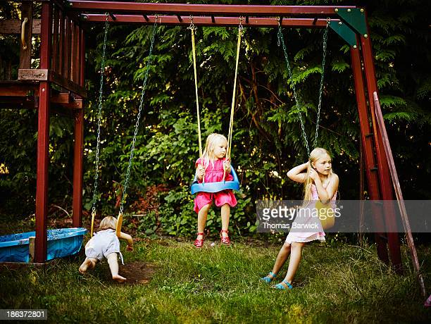 Three sisters playing on swing set in backyard