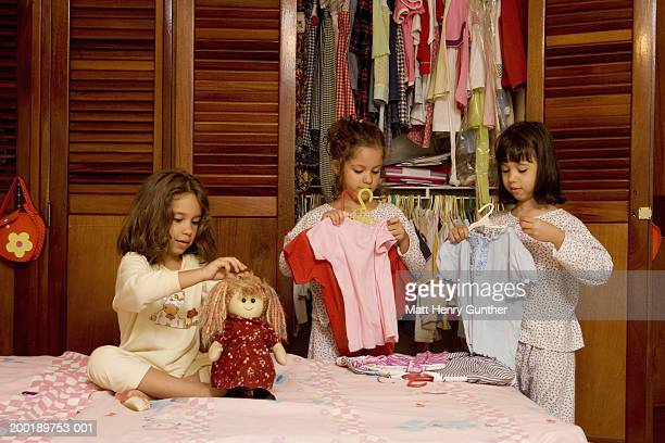 Three sisters (3-6) playing with doll and putting clothes on hangers