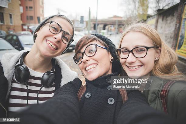 Three sisters taking selfie on street
