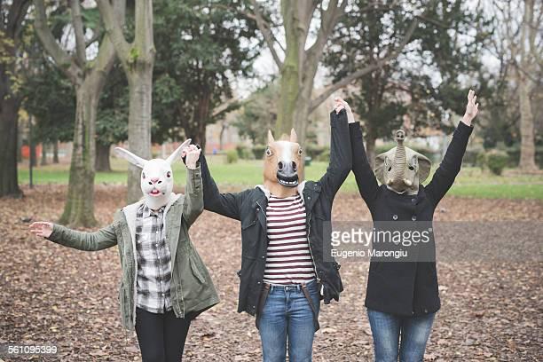 Three sisters wearing animal masks dancing in park