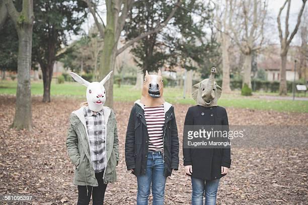 Three sisters wearing animal masks posing in park