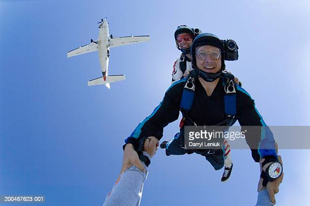 Three skydivers freefalling, low angle view