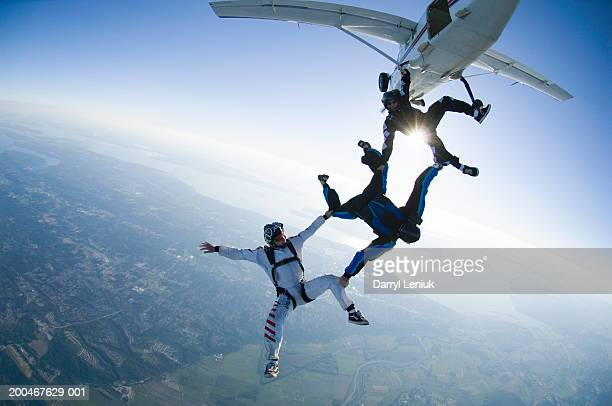 Three skydivers jumping out of airplane, aerial view