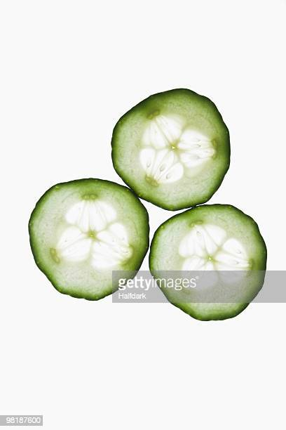 Three slices of an organic cucumber on a lightbox