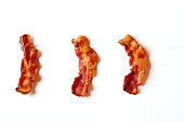 Three slices of fresh fried bacon lined up in a row isolated on a white background