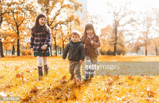 Three small children having fun in the park and running.