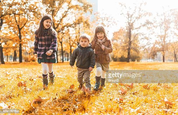 Trois petits enfants s'amuser dans le parc et la course.