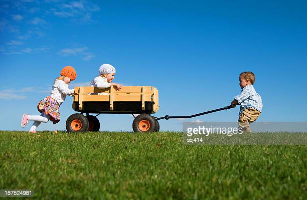 Three Small Children Pushing, Pulling and Playing with Wagon