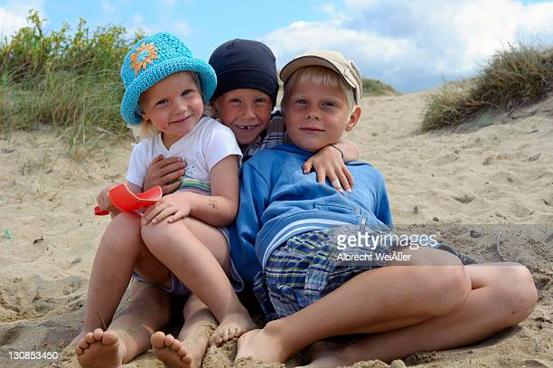 Three small children sitting together on the beach, Bretagne, France, Europe