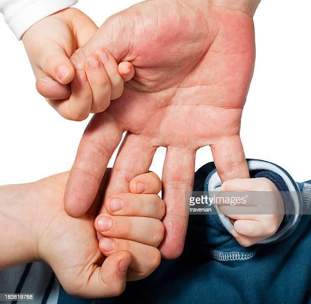 Three smaller hands grabbing onto one bigger hand