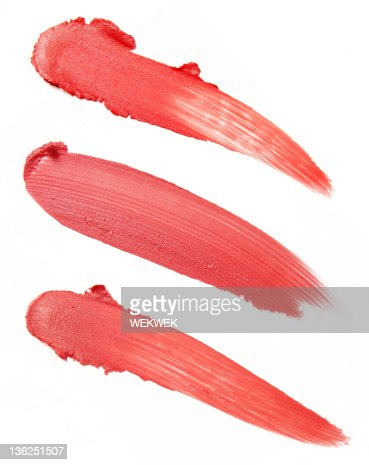 Three smears of red lipstick on a white background