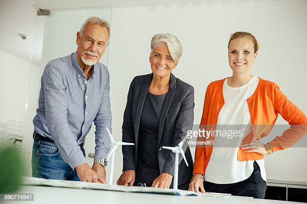 Three smiling business people with wind turbine model on conference table