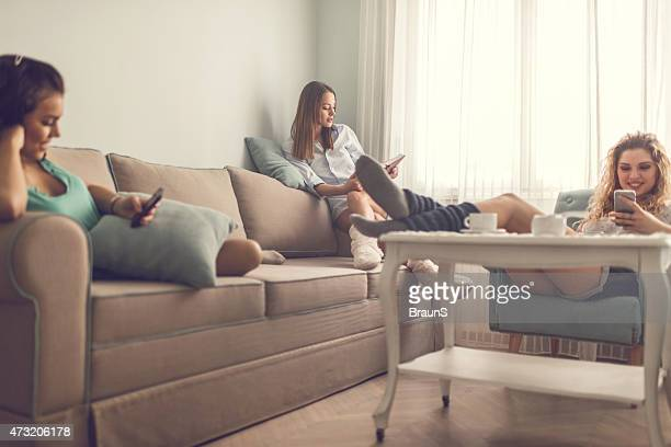 Three smiling female roommates relaxing in the living room.