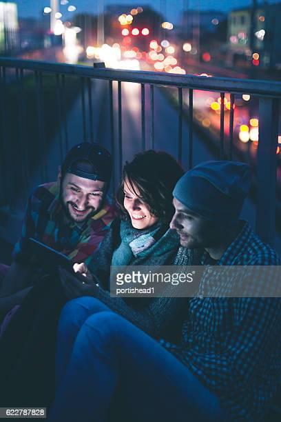 Three smiling friends using digital tablet on bridge by night