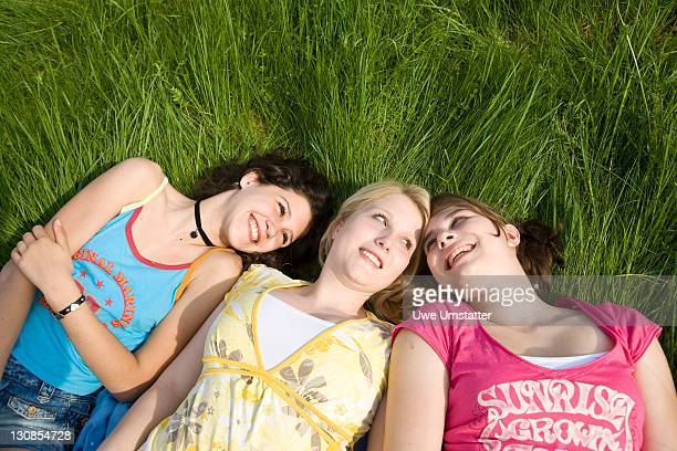 Three smiling girls lying in the grass, smiling