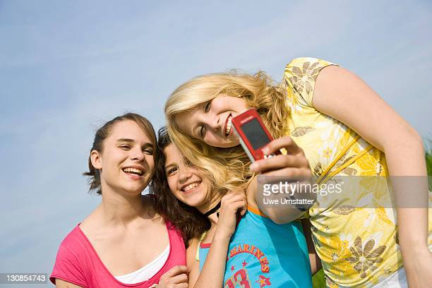 Three smiling girls taking a photo of themselves with a mobile phone