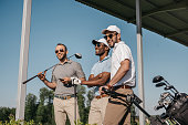Three smiling men in sunglasses holding golf clubs outdoors