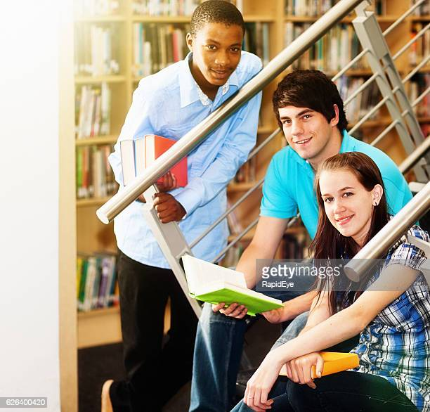 Three smiling students sit on library stairs to study together