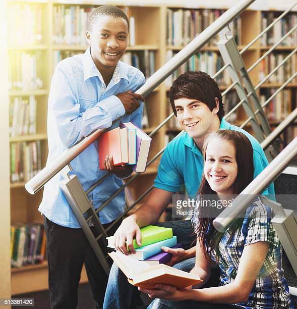 Three smiling students study together in the library