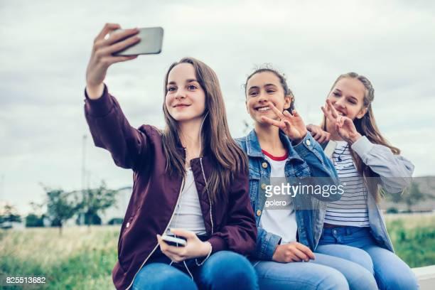 three smiling teenage girls taking selfie outdoors