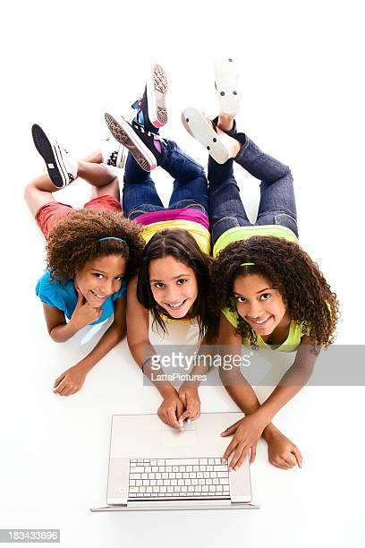 Three smiling teenagers using laptop lying on floor looking up