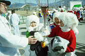 Three snow children hold the Olympic torch during an opening ceremony rehearsal for the 1998 Winter Olympic games
