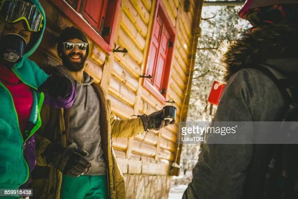 Three snowboarders on winter journey drinking tea