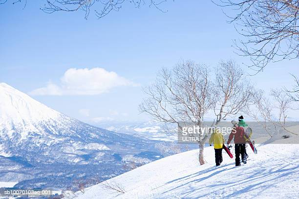 Three snowboarders walking on slope, rear view
