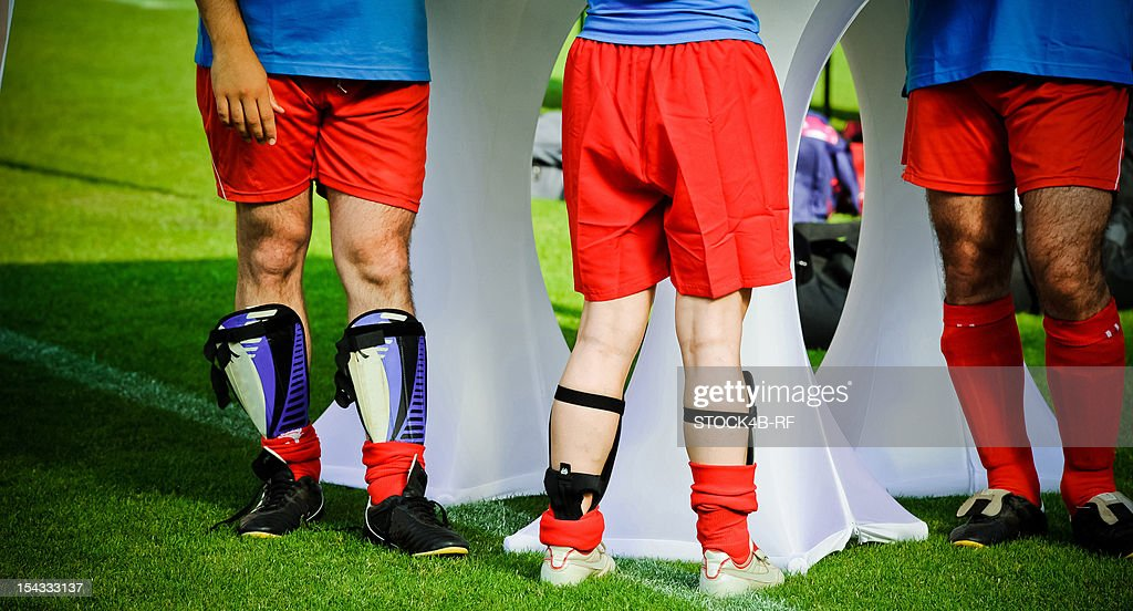 Three soccer players standing on soccer pitch : Stock Photo
