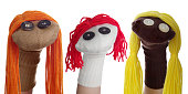 Horizontal image of three sock puppets lined in a row on a white background. One puppet was created using a tan sock with orange hair, one puppet was made with a white sock and red hair, the third pup
