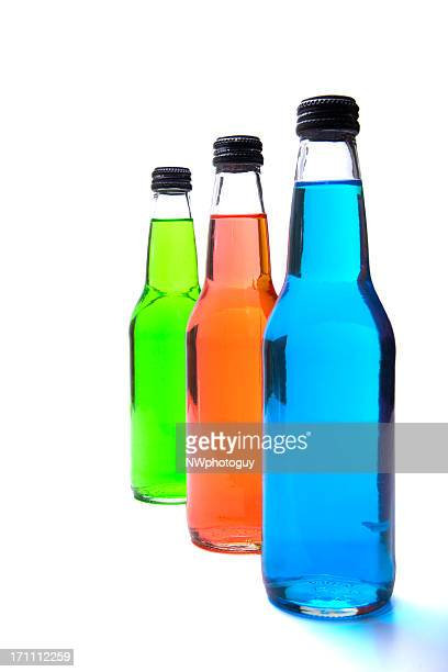 Three soda bottles in green, orange and blue