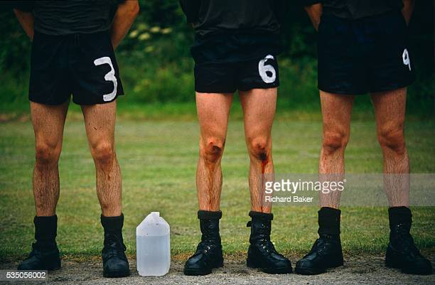 Three soldier recruits wearing shorts and black army boots one with blood trickling down from the knees to the shins stand at ease lined up for...