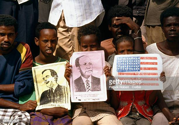 Three Somali children hold drawings welcoming United States President George HW Bush and Major General Mohammed Siad Barre President and dictator of...
