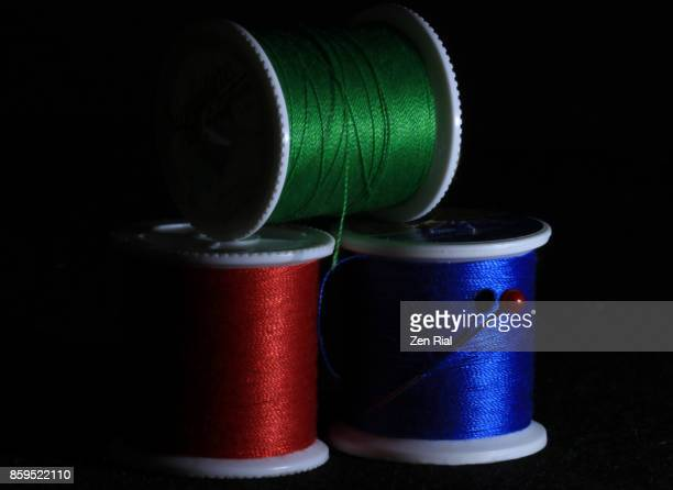 Three spools of thread in primary colors against black background