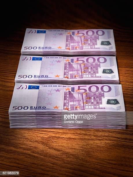 Three stacks of 500 euro bills on office desk